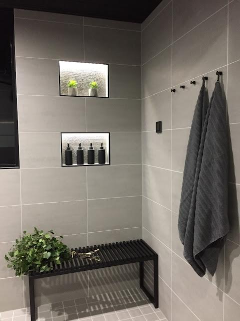 harmaa pesuhuone, musta penkki, jysk, musta pyyhekoukku, musta laattalista, harmaa kylpyhuone