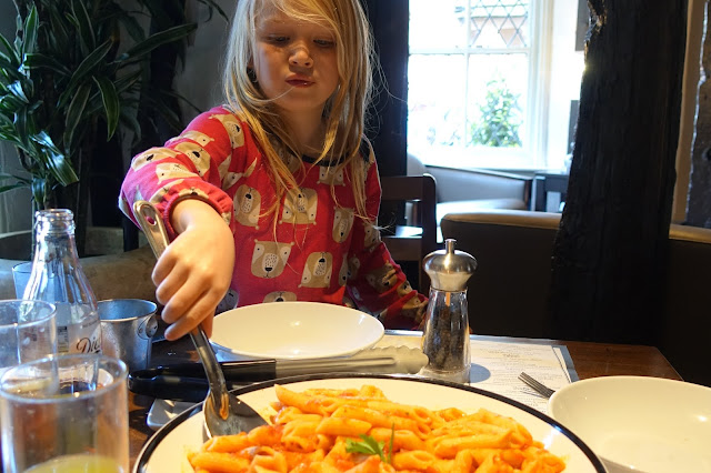 A young girl helping herself to pasta from a big bowl in the middle of the table at Prezzo
