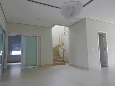 Visão parcial da sala de jantar e estar, antes da instalação do mobiliário, com acesso facilitado para o cômodo reversível e para a escada de perfil aparente.