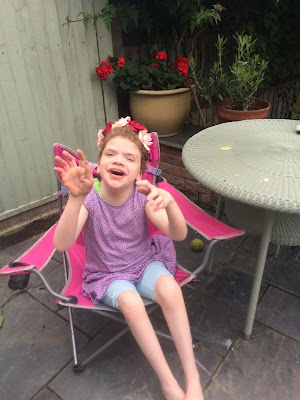 picture of daisy in a pink garden chair smiling and waving at the camera