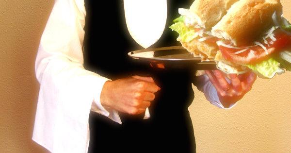 detalle de garzón con sandwich de pescado