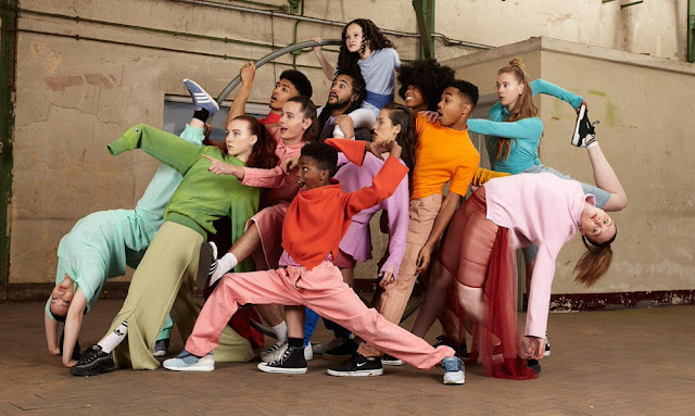 A group of dancers posing as a group in multi-coloured clothing.