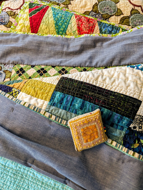 Chambray tubes are hand sewn to the tops of the backs of quilts so they can be hung in a show.