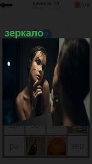 Девушка смотрит сама на себя через зеркало и думает