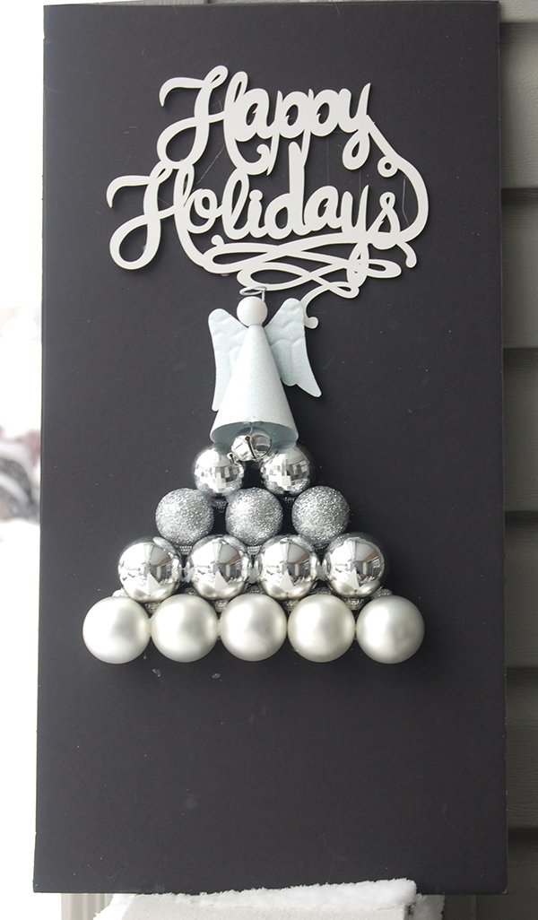 White Happy Holidays sign, white glitter ornament, silver ornament bulbls on black foam board