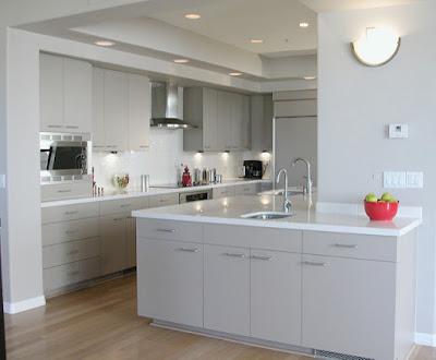 Grande cuisine moderne et blanche, avec de vastes plans de travail.