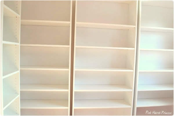 wall of white ikea billy shelving for shoes in shoe room