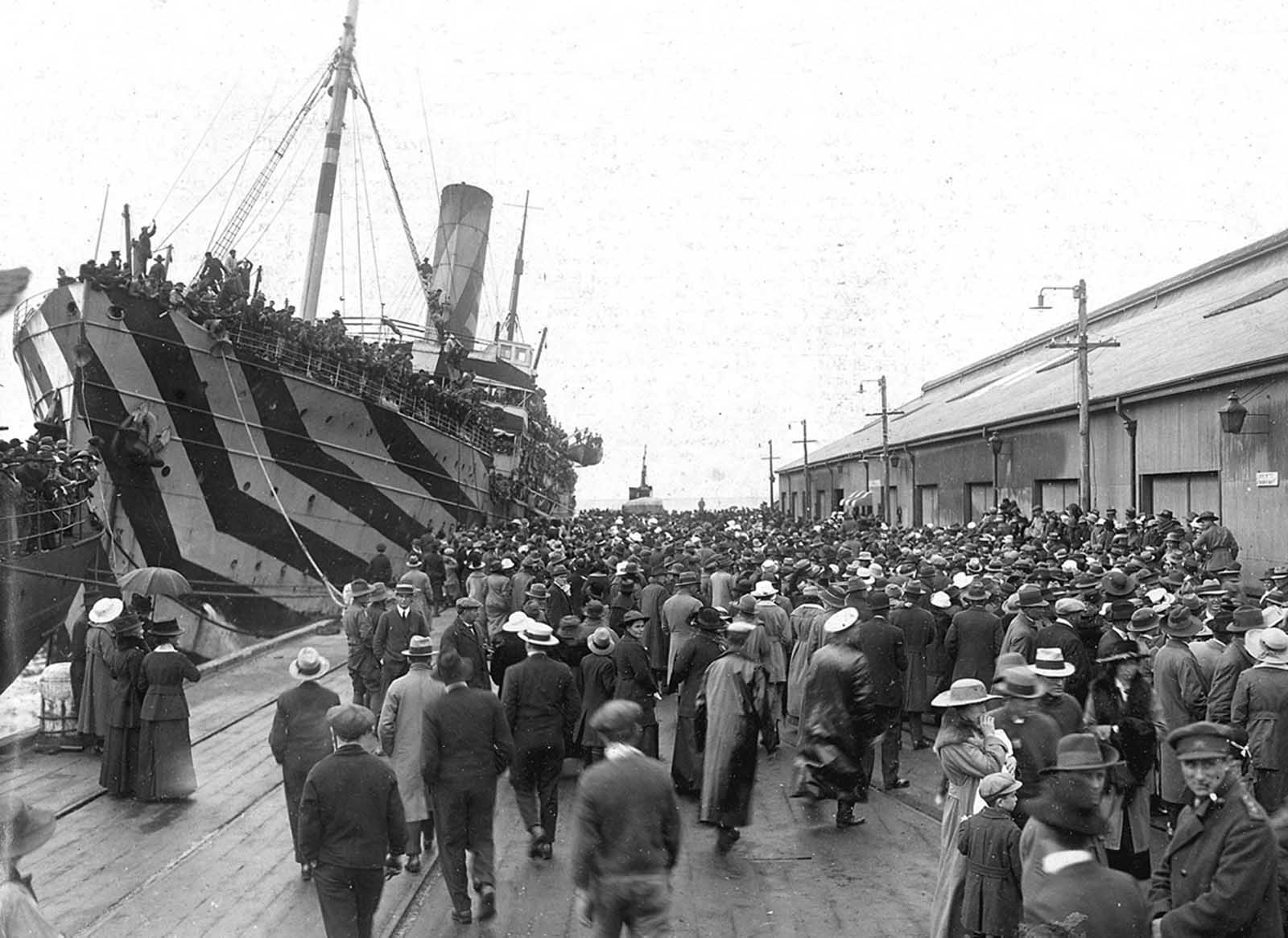Crowds on a wharf at Outer Harbour, South Australia, welcoming camouflaged troop ships bringing men home from service overseas, circa 1918.