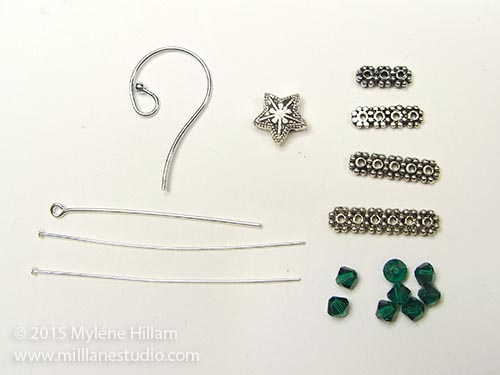 The components you'll need to make the earrings: daisy spacer bars in graduating sizes and emerald Swarovski bicones.