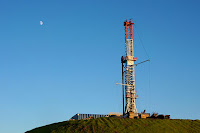 The distant moon looking down on a Marcellus Shale natural gas drill (Credit: copyright by Andrewmits | Dreamstime.com) Click to Enlarge.