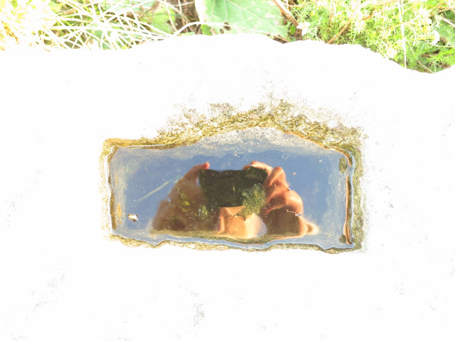 Hands holding camera and blue sky reflected in water on large cube of Portland stone.