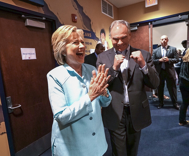 image of Hillary Clinton and Tim Kaine backstage before their first joint appearance as running maters; Hillary is grinning widely and clapping her hands together; Tim is grinning and making two fists
