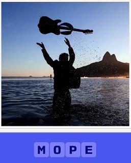 мужчина стоит в море и подбрасывает гитару на верх