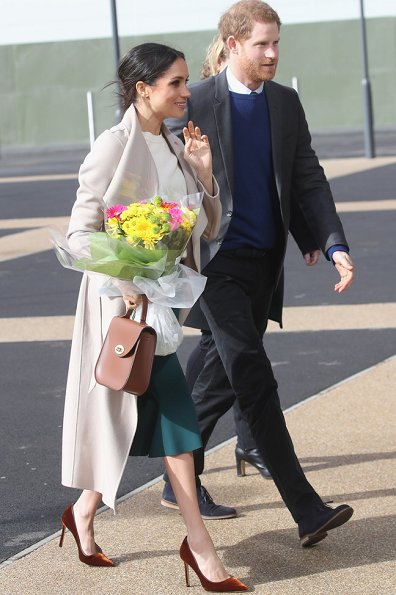 Meghan Markle wore Victoria Beckham cashmere sweater, Mackage Mia sand belted wool coat, Manolo Blahnik shoes and carried Charlotte Elizabeth bag