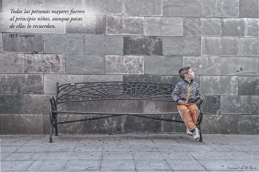 Niño sentado en un banco con frase del Principito