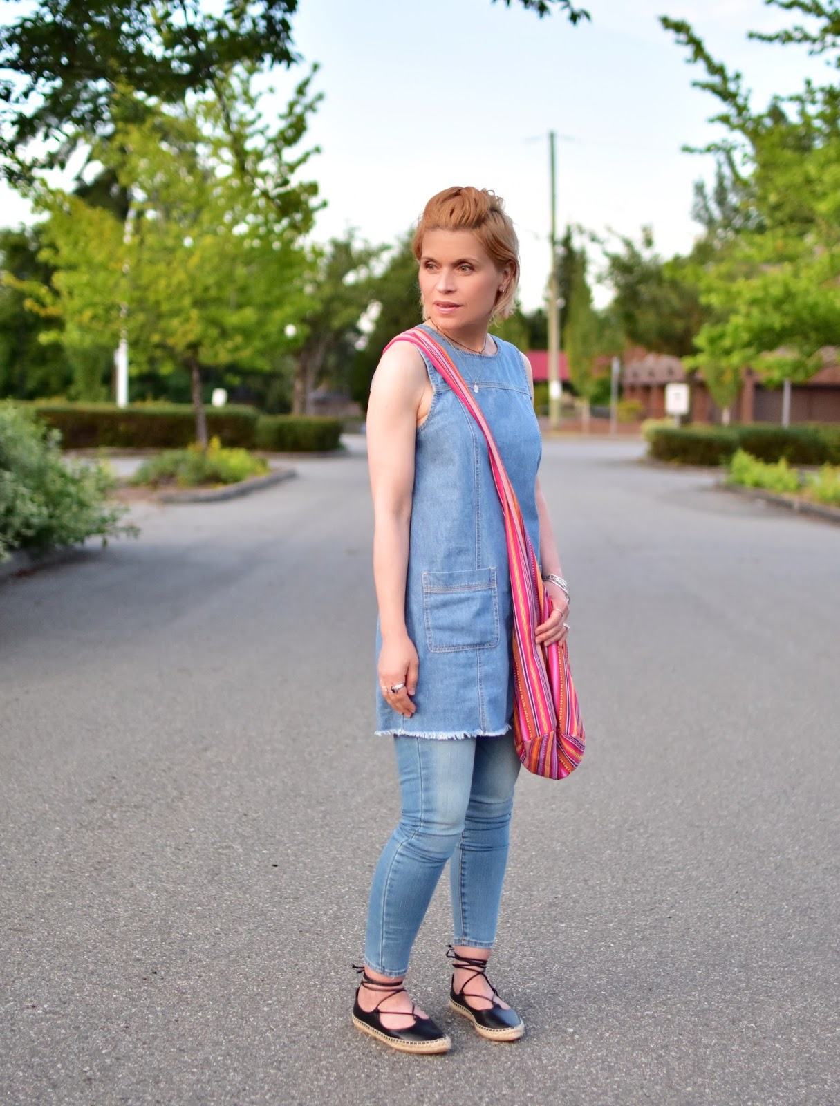 styling a denim tunic with skinny jeans, Zara espadrilles, and a striped hobo bag