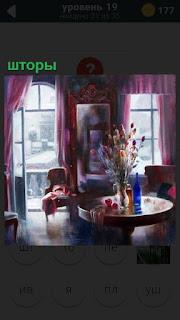 В комнате на окна повешены красные шторы и открыты, стоит стол и стулья