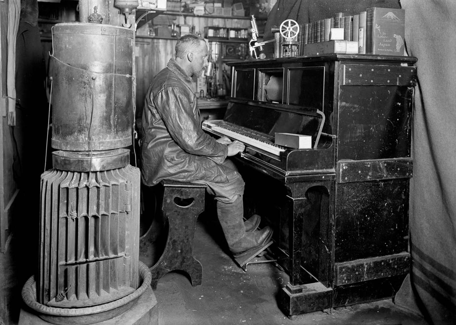 Dog handler Cecil Meares at the piano in the hut. January, 1912.