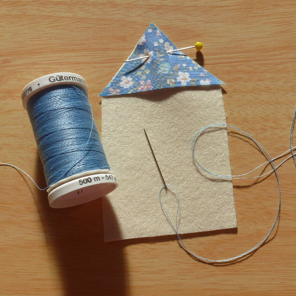 Blue Gutermann thread spool used for sewing fabric on to felt sewing thread and needle