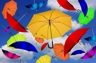 Colorful umbrellas floating in a blue sky with puffy white clouds