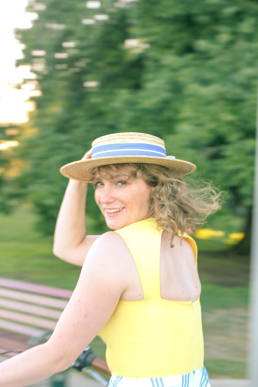 Liana of @findingfemme wears a Laura Ashley straw boater, Nishe dress on her Lekker bike.