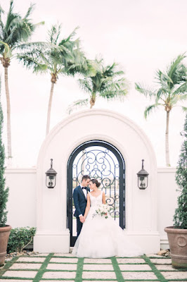 bride and groom posing in front of gate