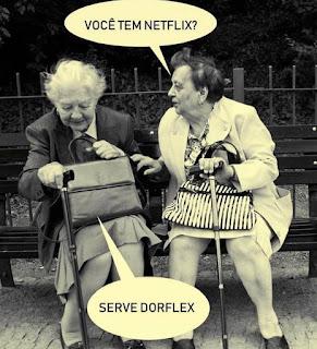 Foto em preto-e-branco de duas senhoras bem idosas sentadas em um banco de praça. Usam casacos sobre as blusas e saias. Descansam as bolsas sobre os colos e seguram com uma das mãos as bengalas. A senhora da direita pergunta: Você tem Netflix? A outra, olha na direção da bolsa e responde: Serve Dorflex.