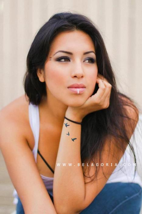 Foto de una bella mujer India, lleva tatuaje de pájaros en el antebrazo