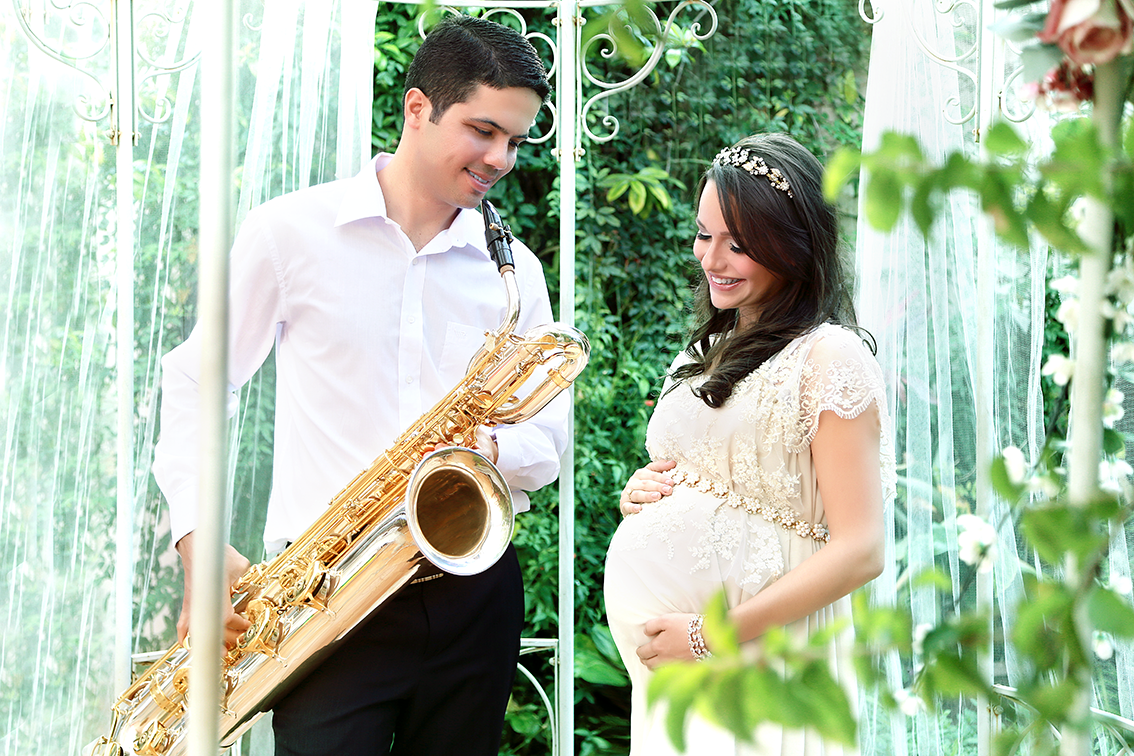foto de gestante e esposo tocando sax em um jardim lindo
