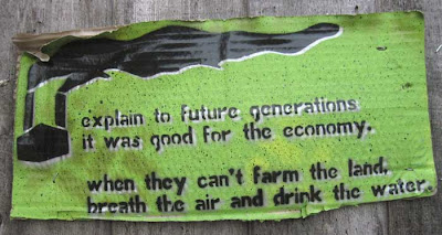 Corrugated cardboard sign, spraypainted green with black smoke-belching factory and words Explain to future generations it was good for the economy. When they can't farm the land, breathe the air and drink the water.