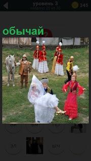 Люди в костюмах на поляне и по обычаю жених на руках несет свою невесту
