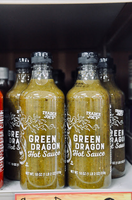 shelf stocked with green hot sauce bottles