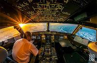 Bir yolcu uçağı güneş batarken bulutlar üzerinde uçarken kokpit içinden görüntüsü