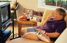 Obesidad y sedentarismo en niños. Niño con sobrepeso, comiendo frente al televisor. Hay una botella de refresco y paquete de snacks, uno de ellos en la mano del chico y el otro sobre la mesa