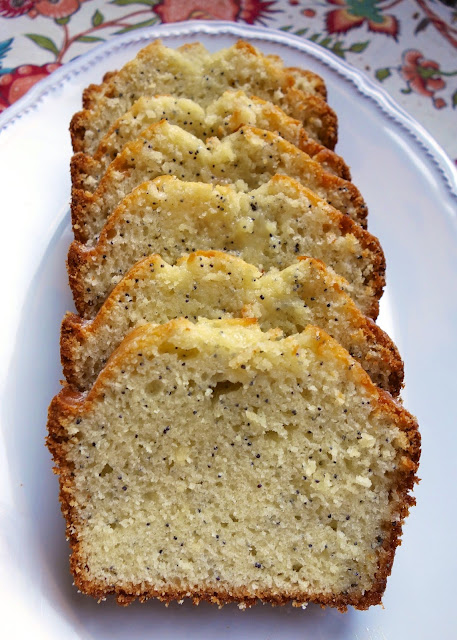 Almond Poppy Seed Bread - seriously delicious sweet bread! This recipe makes two loaves - one for you and one for a friend! Sugar, canola oil, eggs, poppy seeds, lemon juice, almond extract, vanilla, flour, baking powder, salt and milk. Top bread with a quick glaze made with powdered sugar, orange juice, vanilla and almond extract. Great for breakfast or an afternoon pick-me-up! #quickbread #sweetbread