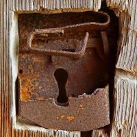 Rusty and broken lock on a wooden door.