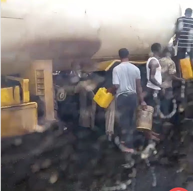 See Nigerians Struggling To Scoop Petrol From Broken Down Tanker
