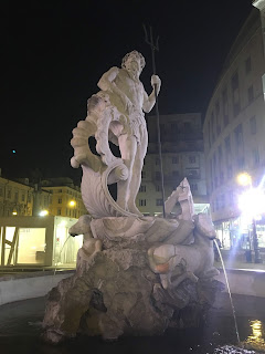 night view of the statue of Neptune at Piazza della Borsa in Trieste
