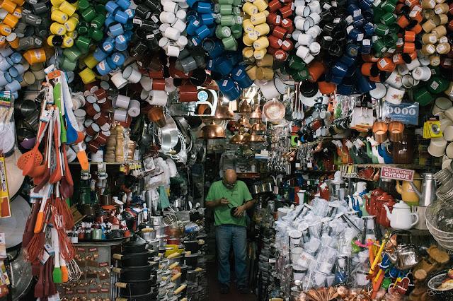 um vendedor se encaminha para o corredor do mercado central em meio à muitos objetos que compõem sua loja, dentre eles canecas de alumínio, cuadores de pano e canecas