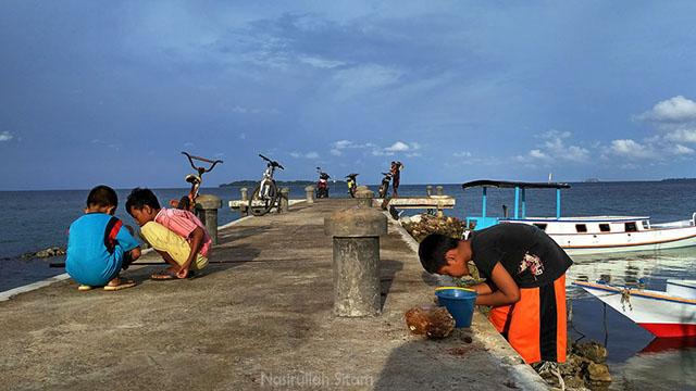 Anak-anak Karimunjawa sedang asyik memancing ikan di pelabuhan