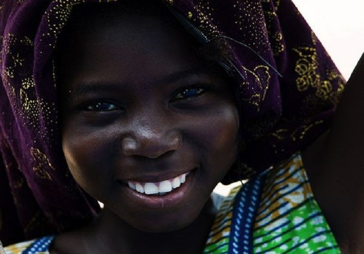 African girl from Burkina Faso smiling. She has really white teeth.