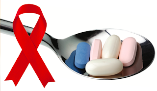 HIV red ribbon next to spoon filled with Rx medicines
