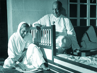 A black and white image of Sardar Patel along with a lady reading a book.