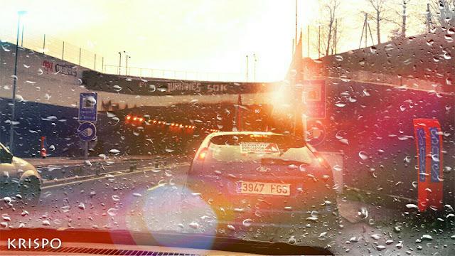 luces de coche y de farola al atardecer a través del parabrisas mojado por la lluvia de un coche en marcha
