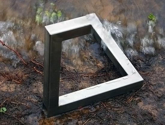 Bir su kenarında imkansız bir şekilde bükülüp kaynatılmış demir profil şekil