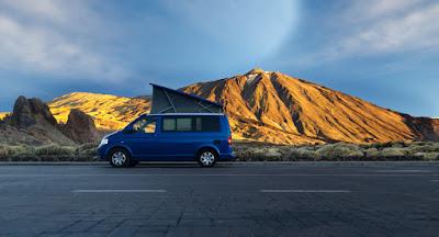 Blue camper van with pop up tent