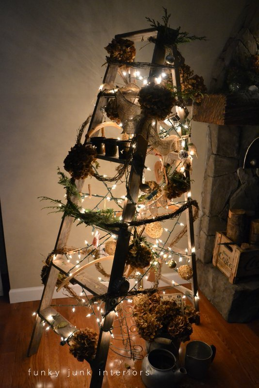 a night picture of a treeless ladder christmas tree decorated with twig garland and hydrangeas