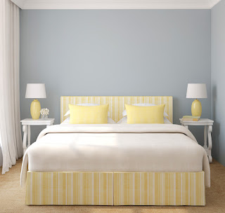A clean yellow and white bed with matching bedside lamps