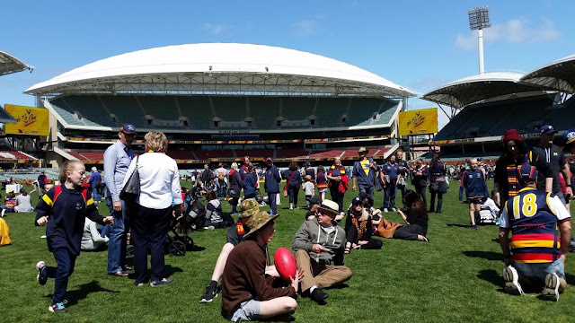 View of the southern stand with families and supporters mingling on the oval.