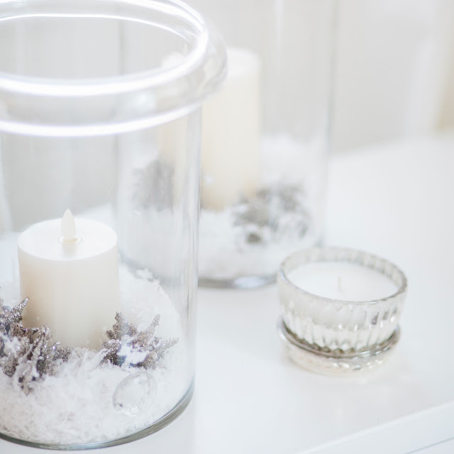 flicker candles with German glitter snowflakes and fake snow displayed in glass hurricanes with lidded mercury glass candle
